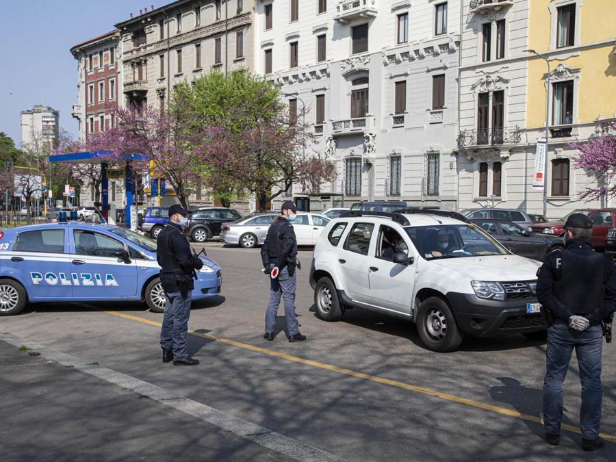 Agenti della polizia eseguono controlli delle autocertificazioni degli spostamenti dei cittadini a Milano, 04 Aprile 2020. (Ansa / Marco Ottico)