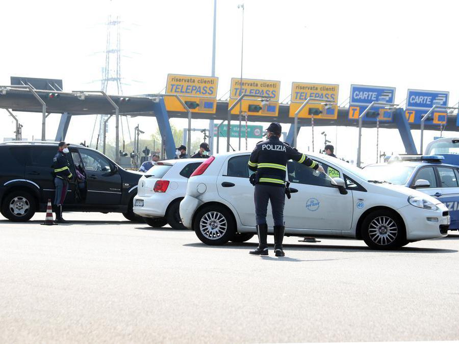 Agenti della Polizia effetuno controlli al casello autostradale di Milano all'imbocco della Auto-laghi A8 e A9, Milano, 04 Aprile 2020. (Ansa / Matteo Bazzi)