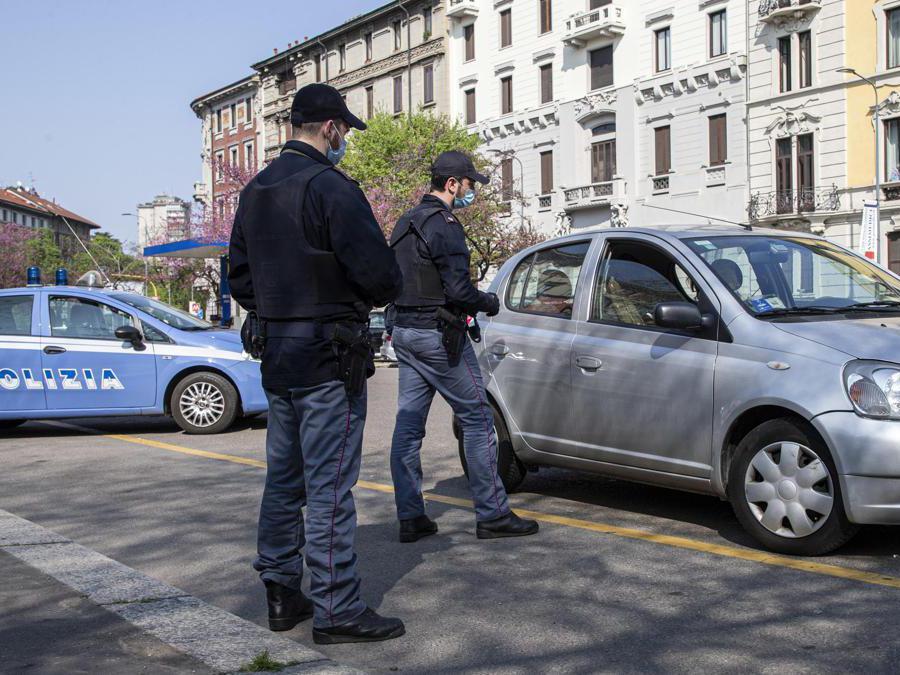 Agenti della polizia eseguono controlli delle autocertificazioni degli spostamenti dei cittadini a Milano, 04 Aprile 2020 (Ansa / Marco Ottico)