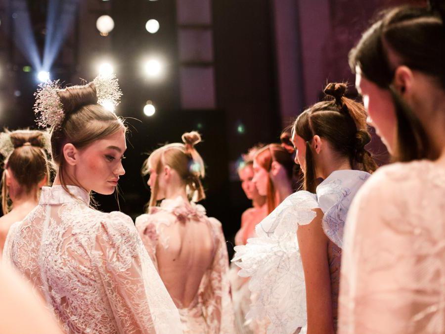 Acconciature per sfilata di Lana Müller by La Biosthétique, official Beauty Partner della Mercedes-Benz Berlin Fashion Week (MBFW)lo stile Geisha interpretato in modo spettacolare con fiori e vari loop dall'alto in basso.