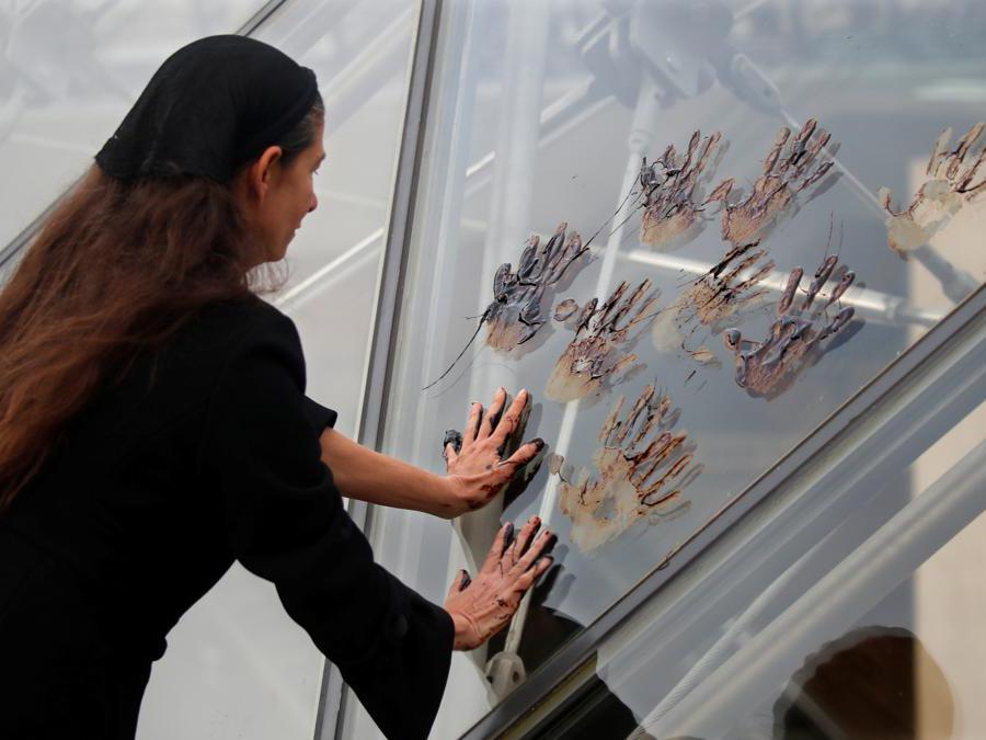 Parigi, Francia, 27 settembre 2019, un'attivista lascia l'impronta delle mani sporche di petrolio sul vetro della Piramide del Museo del Louvre (REUTERS/Charles Platiau)