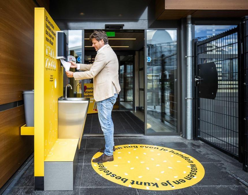 Un uomo disinfetta le mani all'entrata di un  McDonald's ,  Arnhem, The Netherlands (EPA/REMKO DE WAAL)