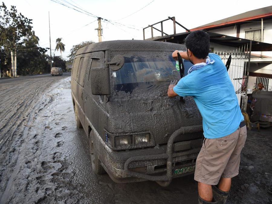 Un residente pulisce fango e cenere dalla sua auto dopo che il vulcano Taal ha iniziato a eruttare cenere sulla città di Tanauan, provincia di Batangas a sud di Manila. (Photo by Ted ALJIBE / AFP)