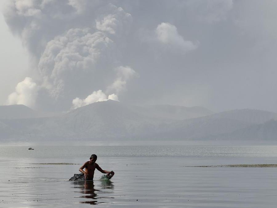 Un pescatore guada con le sue reti nelle acque del lago Taal mentre il vulcano Taal emette cenere visto dalla città di Tanauan nella provincia di Batangas, a sud di Manila. (Photo by Ted ALJIBE / AFP)