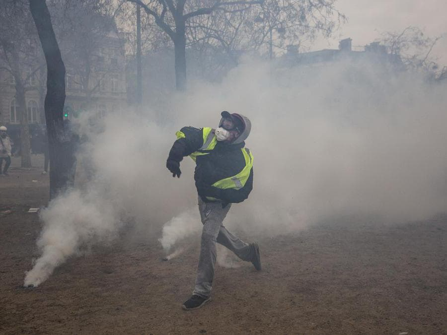 On Charles de Gaulle square, a demonstrator throws a projectile at the police in the middle of the tear gas. Yellow vests demonstration - Act IX - Paris on 12-01-19 Place Charles de Gaulle. Un manifestant lance un projectile sur la police au milieu des gaz lacrimogènes. Manifestation des gilets jaunes - Acte IX - Paris le 12-01-19