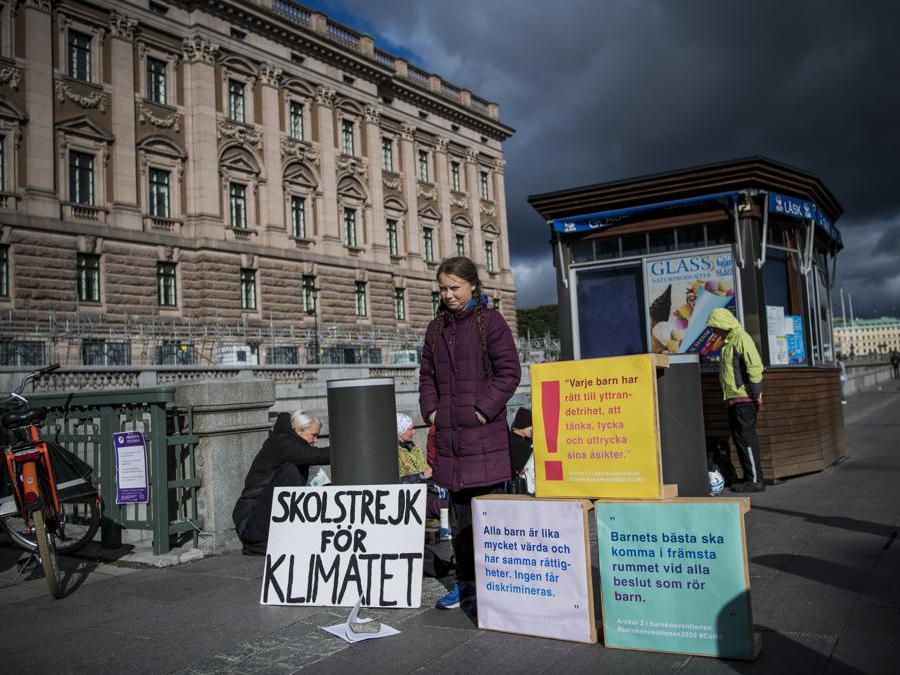 Greta Thunberg di fronte al Parlamento svedese espone dei cartelli con la scritta«Sciopero scolastico per il clima» e «Ogni bambino ha il diritto alla libertà di parola ad avere un'opinione ed esprimere la sua opinione» (Afp/Jonathan Nackstrand)