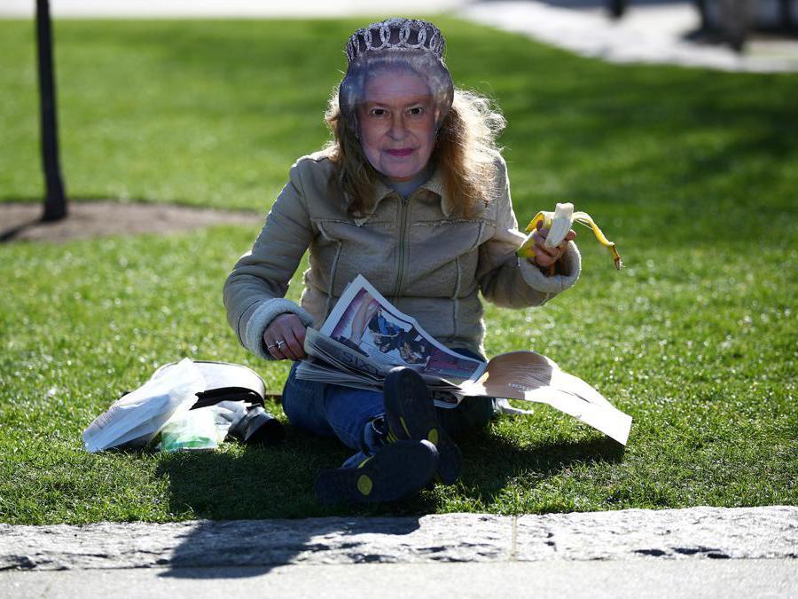 Londra, una donna legge il giornale indossando una maschera raffigurante la Regina Elisabetta (REUTERS/Hannah McKay)