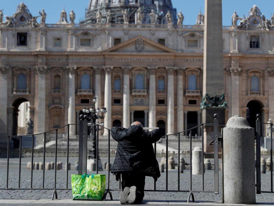 Roma, un uomo inginocchiato in preghiera davanti a una Piazza S. Pietro  deserta (REUTERS/Guglielmo Mangiapane)