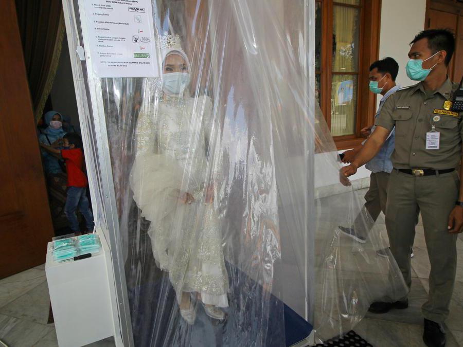 Una sposa indonesiana viene cosparsa di liquido disinfettante (Antara Foto/Moch Asim/via REUTERS)