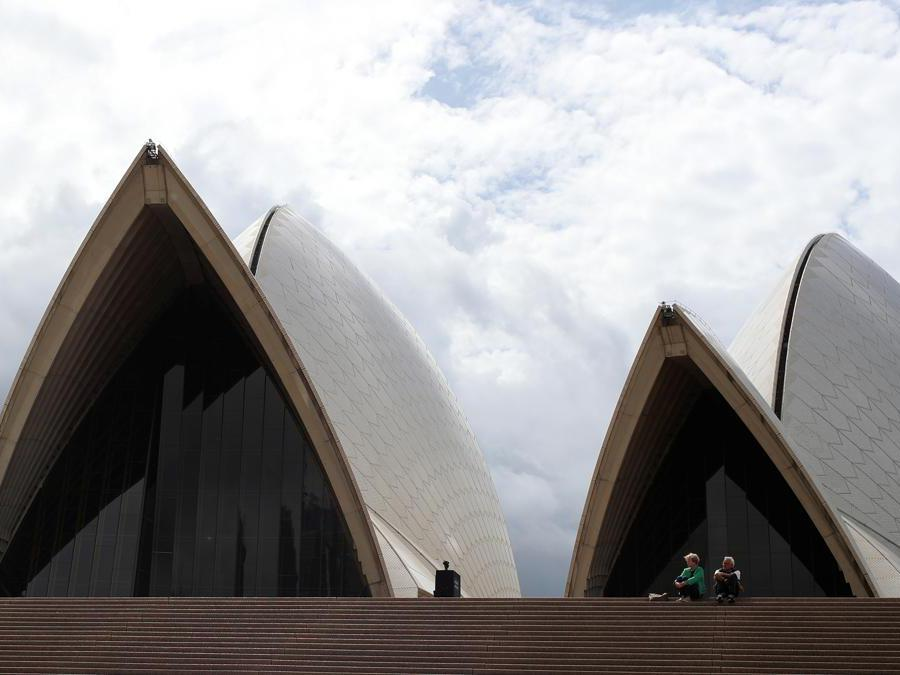 Turisti seduti sulla gradinata di una Sydney Opera House deserta (REUTERS/Loren Elliott)
