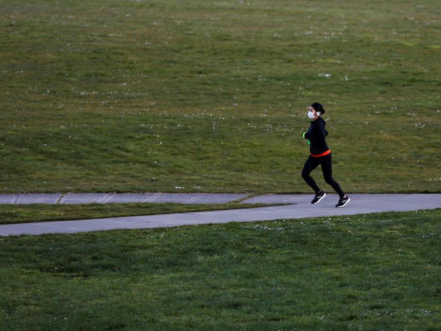 Seattle,  Usa, una donna con la mascherina fa jogging nel parco (REUTERS/Lindsey Wasson)