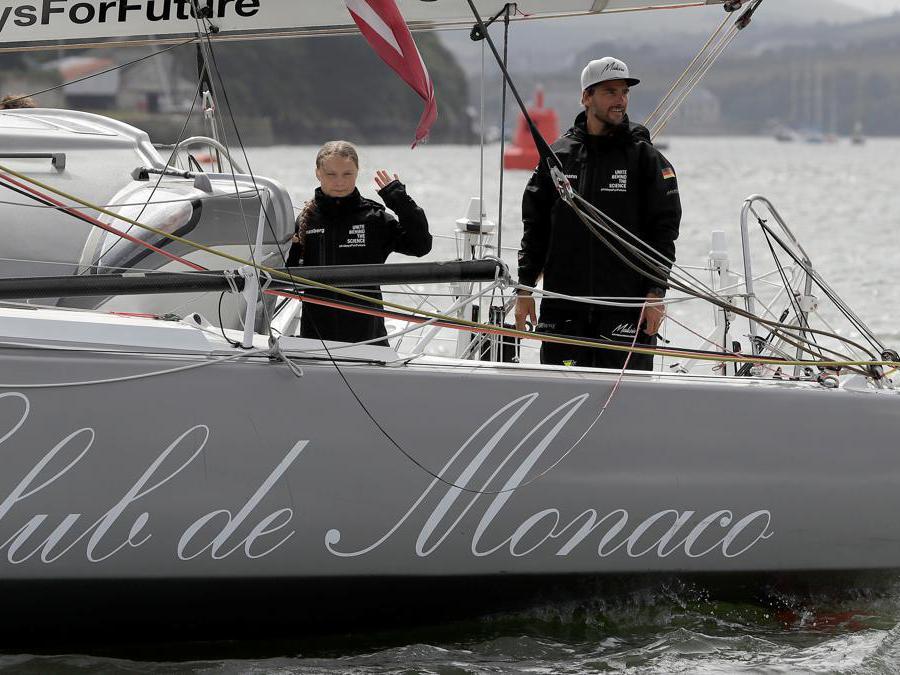 L'attivista svedese per il clima adolescente Greta Thunberg saluta dalla barca  Malizia II accanto al velista tedesco Boris Herrmann, mentre inizia il suo viaggio.  Kirsty Wigglesworth/Pool via REUTERS