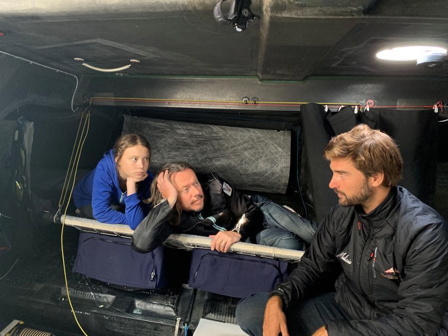 L'attivista per ilclima Greta Thunberg, suo padre Svante  (centro) e lo skipper Boris Herrmann (destra) siedono a bordo dello yacht  Malizia II. Team Malizia/Handout via REUTERS
