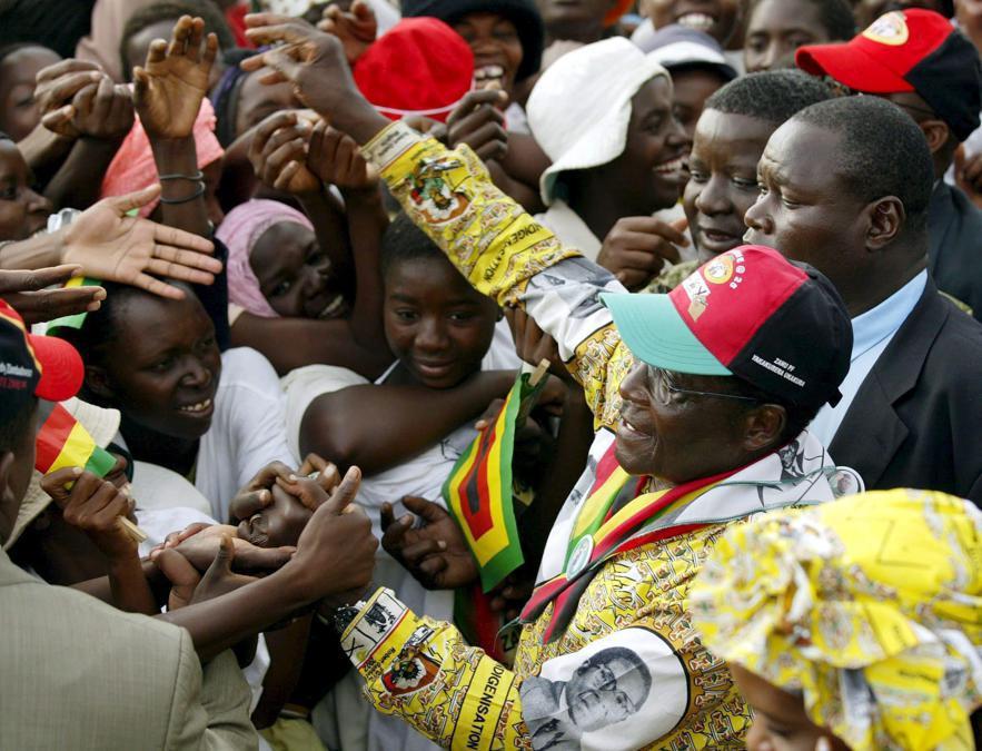 Una foto del 23 marzo 2005 mostra il presidente Robert Mugabe (destra, in giallo) dello Zimbabwe che stringe la mano ai sostenitori del suo partito ZANU (PF) durante una manifestazione elettorale nella città di Tsholotsho nello Zimbabwe sud-occidentale. EPA