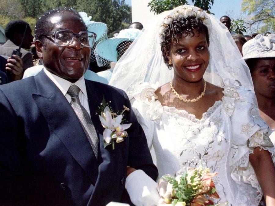 Il presidente Robert Mugabe e la nuova moglie Grace lasciano la chiesa cattolica di Kutama nello Zimbabwe il 17 agosto 1996 dopo aver scambiato i voti nuziali. REUTERS/Howard Burditt/File Photo