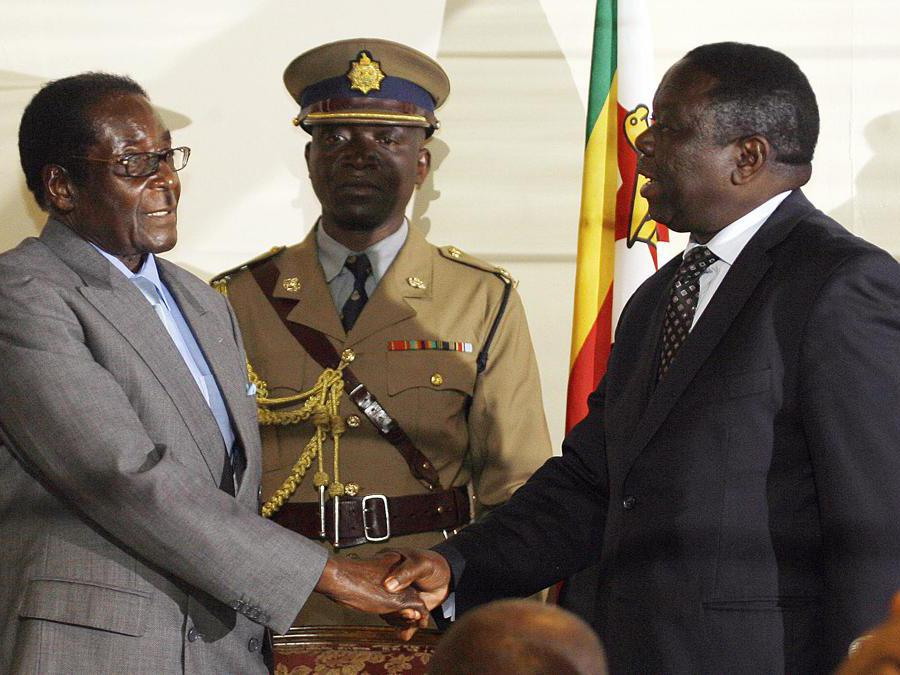 In questa foto  scattata il 21 luglio 2008, il presidente dello Zimbabwe  Robert Mugabe (sinistra) stringe la mano al leader del Movimento per il cambiamento democratico Morgan Tsvangirai ad Harare. (Photo by DESMOND KWANDE / AFP)