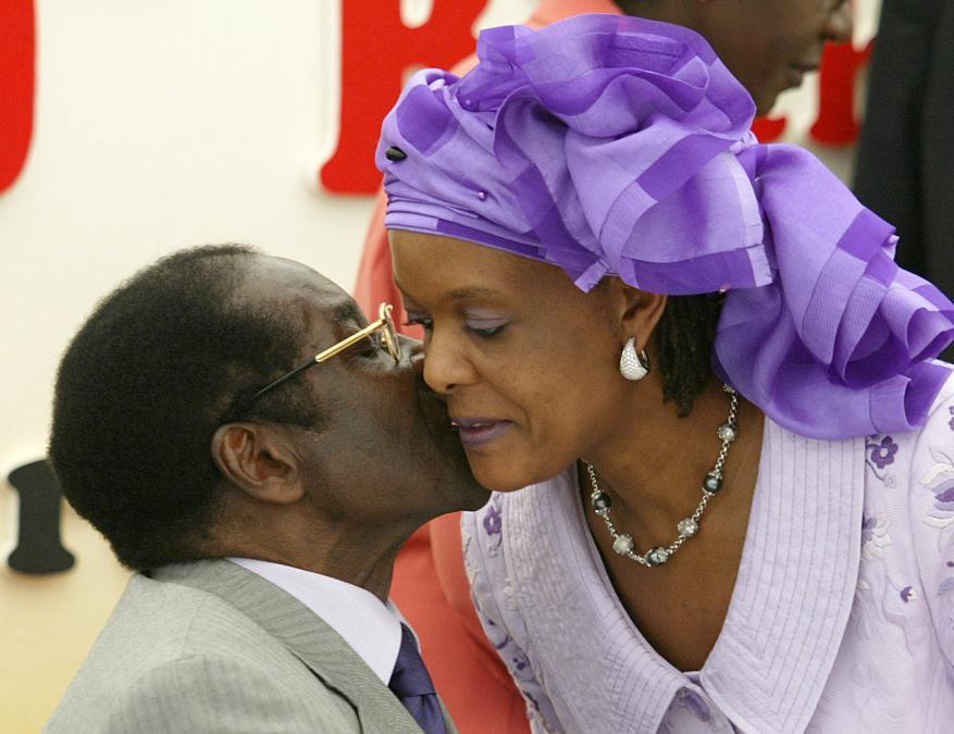 Il presidente dello Zimbabwe Robert Mugabe viene baciato dalla moglie Grace alla sua festa per l'ottantesimo compleanno nella sua zona natale di Zvimba, a ovest di Harare, il 21 febbraio 2004. REUTERS/Howard Burditt/File Photo
