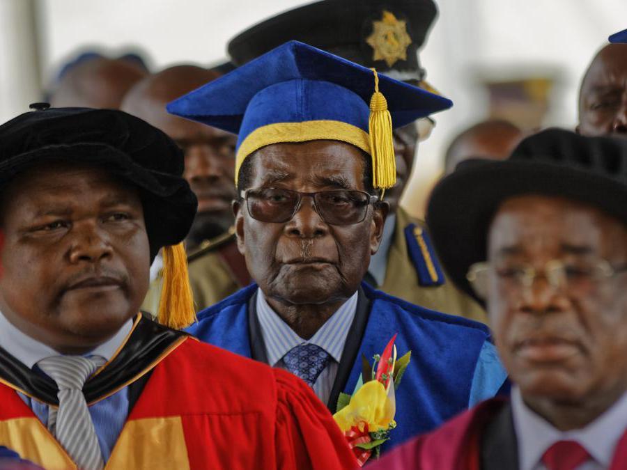 17 novembre 2017. Il presidente dello Zimbabwe, Robert Mugabe, al centro, arriva per presiedere a una cerimonia di laurea degli studenti presso la Zimbabwe Open University alla periferia di Harare, Zimbabwe. (AP Photo/Ben Curtis, File)
