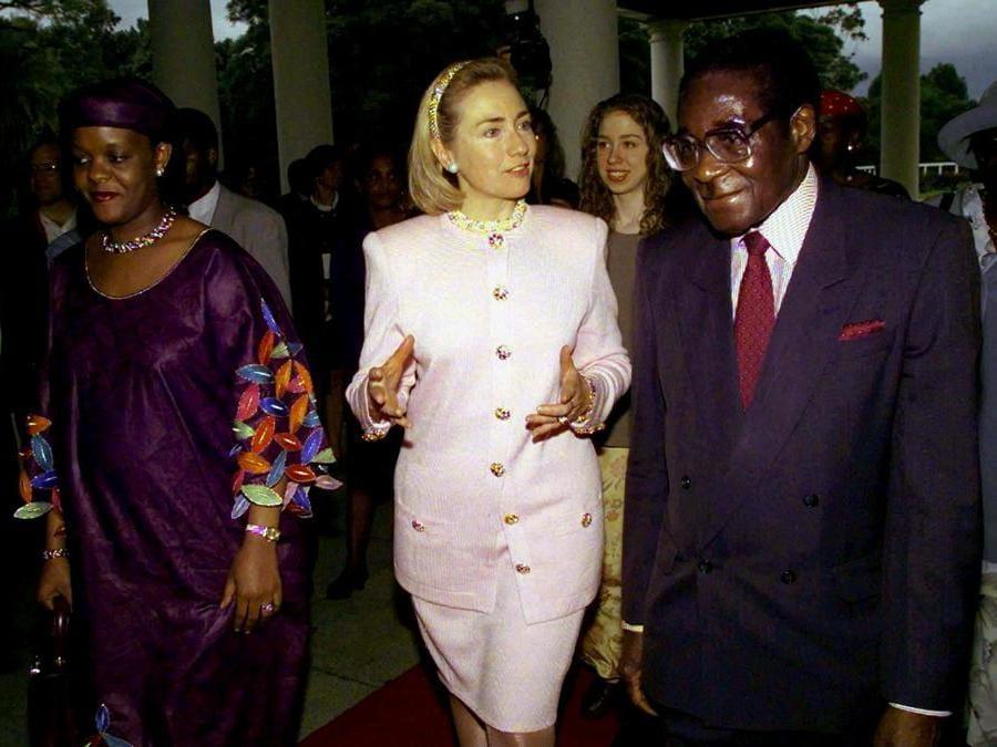 La First Lady americana Hillary Clinton (centro) è scortata dal presidente dello Zimbabwe Robert Mugabe (destra) e da sua moglie Grace Mugabe dopo essere arrivata al palazzo presidenziale di Harare il 21 marzo 1997. REUTERS/Win McNamee/File Photo