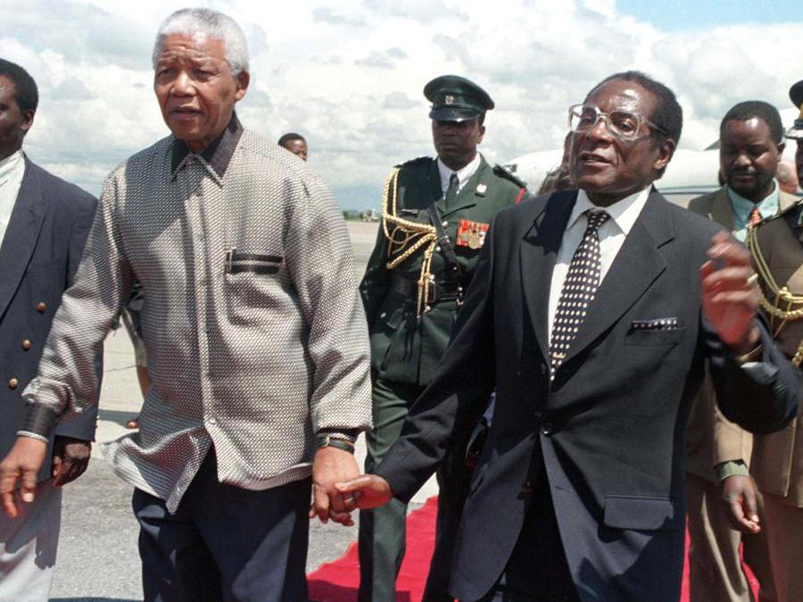 Il presidente Robert Mugabe dello Zimbabwe (destra)  con il suo omologo sudafricano Nelson Mandela che lo saluta al suo arrivo nel paese il 13 dicembre 1998. REUTERS/Howard Burditt/File Photo