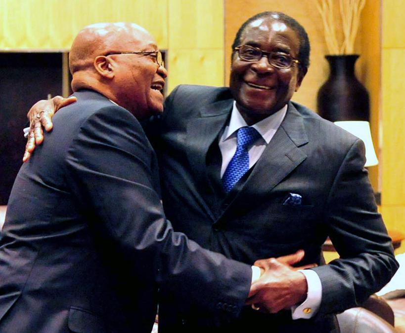 Una foto distribuita dal governo sudafricano mostra il presidente sudafricano Jacob Zuma (sinistra) e il presidente dello Zimbabwe Robert Mugabe (destra) che si abbracciano durante una riunione straordinaria della SA Development Community (SADC) presso il Sandton Convention Center di Johannesburg, in Sudafrica, il 20 giugno 2009 .EPA