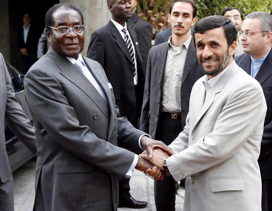 Il presidente iraniano Mahmoud Ahmadinejad (destra) stringe la mano al presidente dello Zimbabwe Robert Mugabe (sinistra)  presso l'ufficio presidenziale di Teheran, Iran, 20 novembre 2006 . EPA/ABEDIN TAHERKENAREH