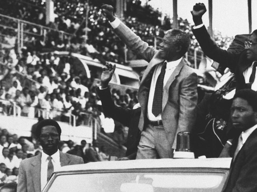 In questa foto del 5 marzo 1990, il vice presidente del Congresso nazionale africano Nelson Mandela, al centro, e il presidente dello Zimbabwe Robert Mugabe, all'estrema destra, salutano la folla all'inizio del nuovo giorno festivo dello Zimbabwe, Mandela Day, a Harare, Zimbabwe. (AP Photo/John Parkin, file)