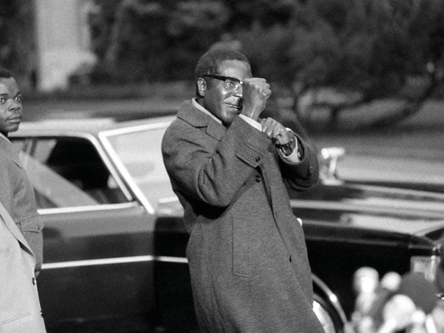 In questa foto di archivio del 4 novembre 1974, Robert Mugabe prende parte alla conferenza di Rhodesia a Ginevra, alza scherzosamente i pugni mentre incontra giornalisti. (AP Photo, file)