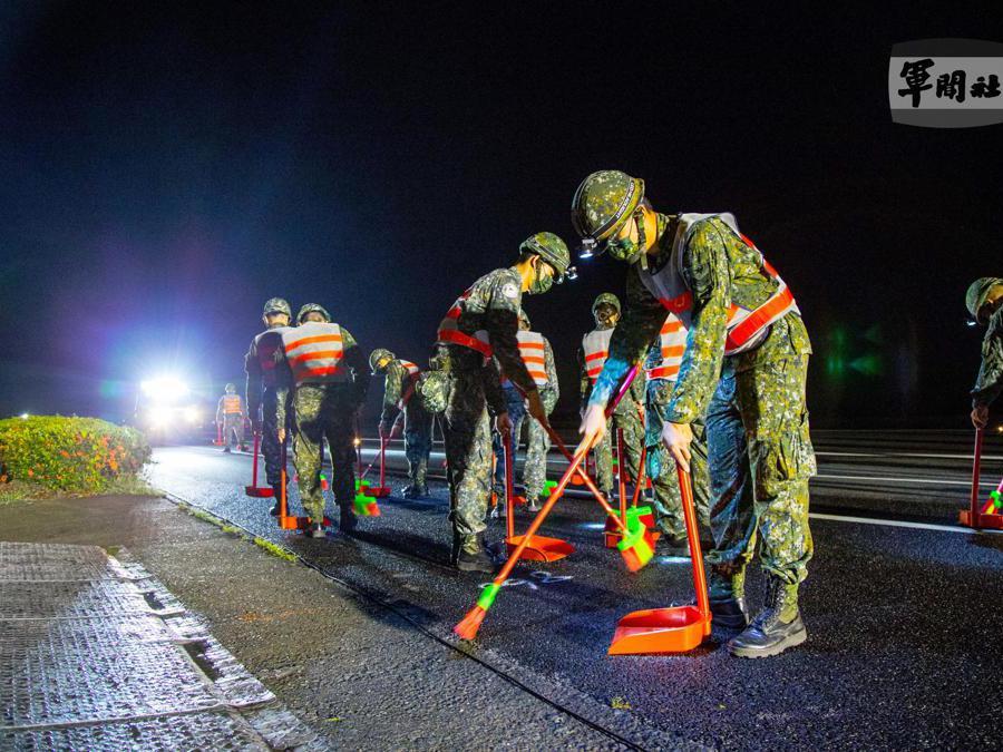 Il personale militare taiwanese  spazza i detriti su un'autostrada convertita in pista durante l'esercitazione di decollo e atterraggio di emergenza a Pingtung, Taiwan. (EPA/TAIWAN MILITARY NEWS AGENCY)