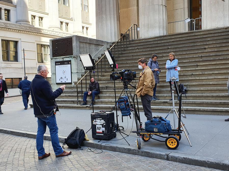 La troupe di una tv finanziaria davanti a Wall Street: un reporter attende il collegamento per raccontare la giornata di Borsa. Dietro la telecamera l'operatore indossa la mascherina.