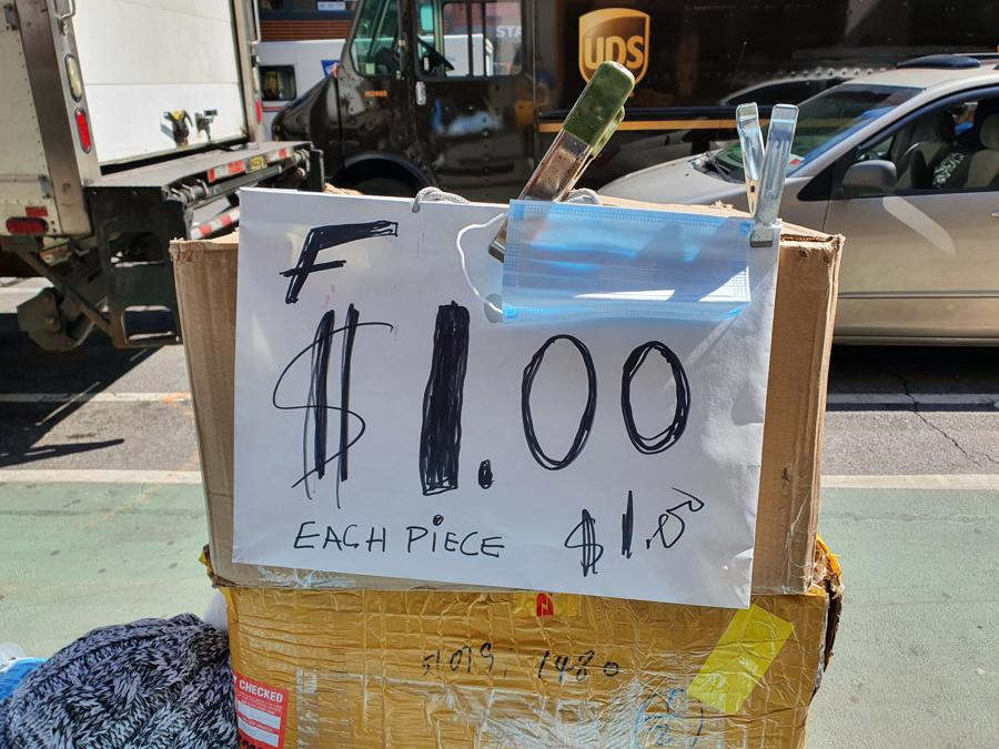 Sulla 6Th Avenue una bancarella improvvisata vende mascherine a un dollaro.