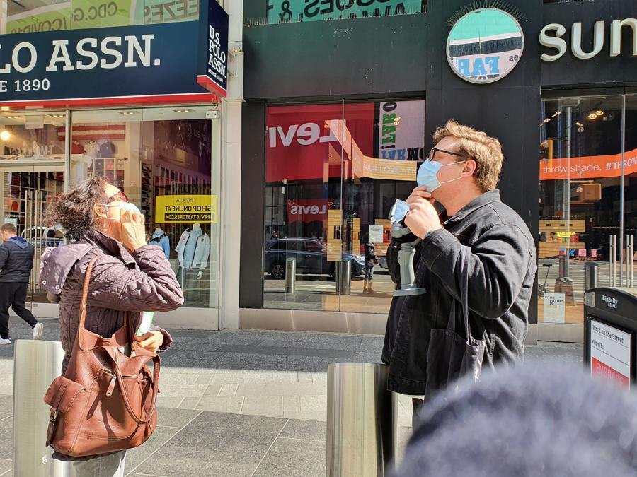 Una signora sinoamericana regala una mascherina a uno studente italiano sui marciapiedi vicino a Times Square: Stay safe.
