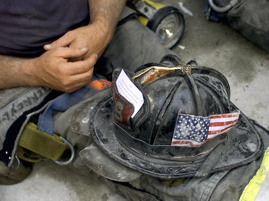 Un vigile del fuoco con l'elmetto sulle gambe durante un momento di riposo nelle operazioni di soccorso. (Photo by Beth A. Keiser / AP Pool / AFP)