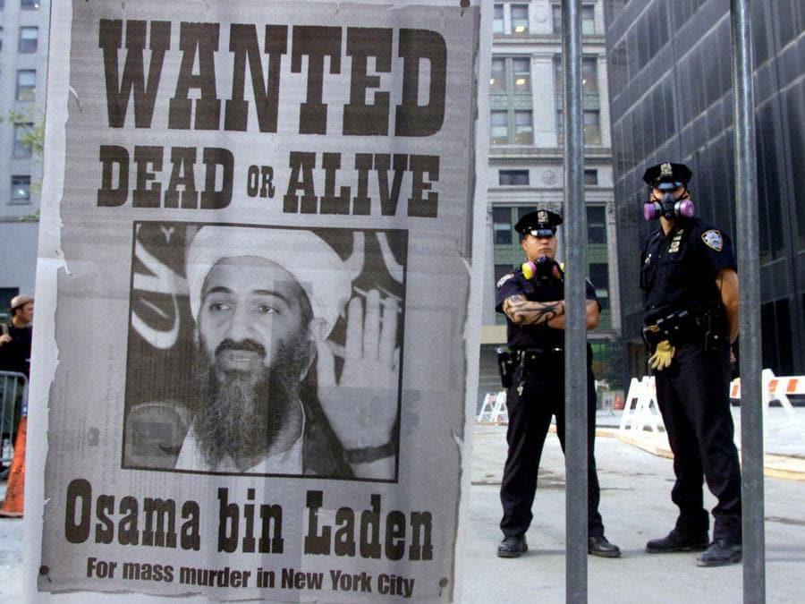 La polizia di New York vicino a un poster a pagina intera di un giornale di New York con l'annuncio della ricerca del terrorista Osama bin Laden. (Reuters / Russell Boyce)