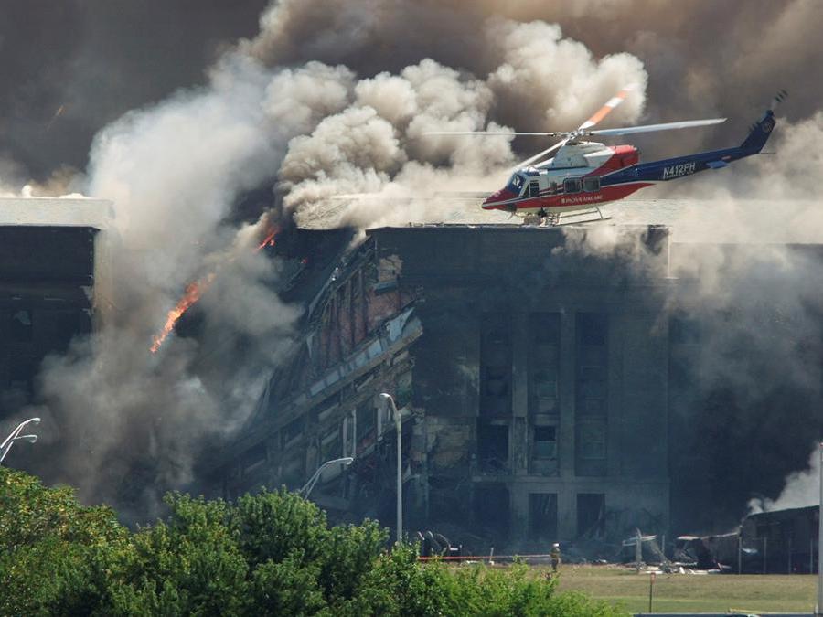 Un elicottero di soccorso esamina i danni al Pentagono mentre i vigili del fuoco combattono le fiamme dopo che un aereo si è schiantato contro il quartier generale militare degli Stati Uniti fuori Washington. (Reuters / Larry Downing)