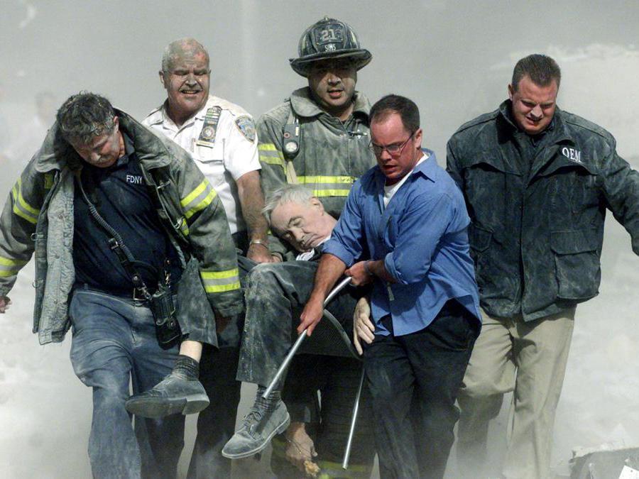 I soccorritori trasportano il cappellano dei vigili del fuoco di New York, ferito a morte, il Rev. Mychal Judge, dal relitto del World Trade Center. Il cappellano è stato schiacciato a morte dalla caduta di detriti mentre dava l'estrema unzione a un uomo nel centro commerciale. (Reuters / Shannon Stapleton/File Photo)