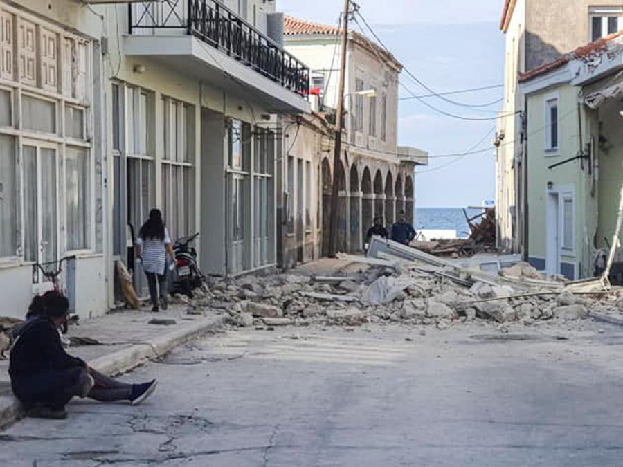 La gente cammina davanti a una casa distrutta dopo il terremoto avvenuto oggi  nell'isola di Samos (Eurokinissi / Afp)