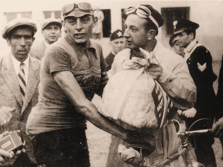 Fausto Coppi durante la consegna di un panettone come premio dopo la vittoria della tappa Firenze-Modena al Giro del 1940  (ANSA/ASSOCIAZIONE FAUSTO E SERSE COPPI)