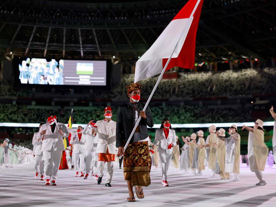 Indonesia's flag bearer Nurul Akmal leads the delegation as they parade during the opening ceremony of the Tokyo 2020 Olympic Games, at the Olympic Stadium, in Tokyo, on July 23, 2021. (Photo by Odd ANDERSEN / AFP)