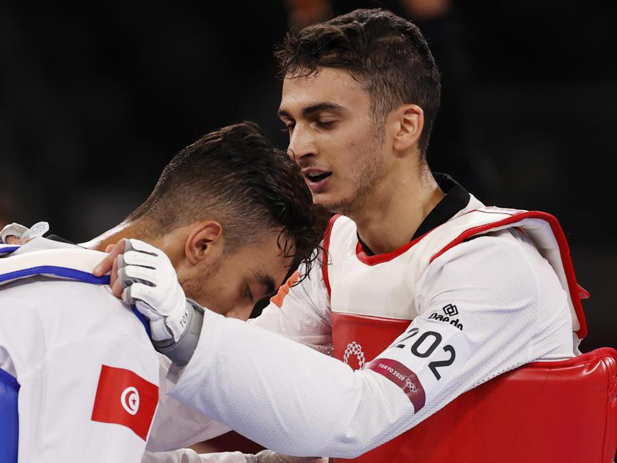 epa09362204 Vito Dell'Aquila (R) of Italy consoles Mohamed Khalil Jendoubi (L) of Tunisia after his loss during their bout in the Taekwondo Men's -58kg Gold Medal Contest of the Tokyo 2020 Olympic Games at the Makuhari Messe convention centre in Chiba, Japan, 24 July 2021. EPA/RUNGROJ YONGRIT