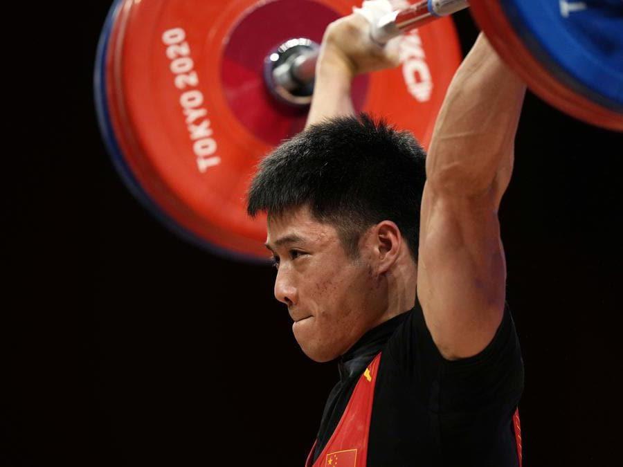 Il cinese Li Fabin nella gara maschile di sollevamento pesi categoria  61 Kg(AP Photo/Luca Bruno)