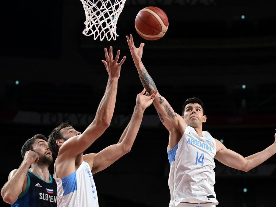L'argentino Gabriel Deck (a destra) e Marcos Delia controlo sloveno Mike Tobey (a sinistra) durante la competizione di basket maschile del gruppo C del turno preliminare tra Argentina e Slovenia. (Afp/Aris Messinis)
