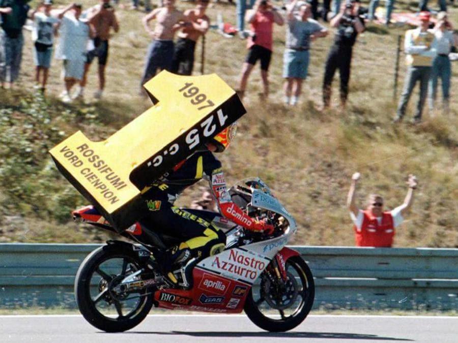 Valentino Rossi mostra trionfante un gigantesco numero 1 per il titolo mondiale delle 125 cc a Brno, in una immagine del 31 agosto 1997. (Ansa/Igor Zehl)