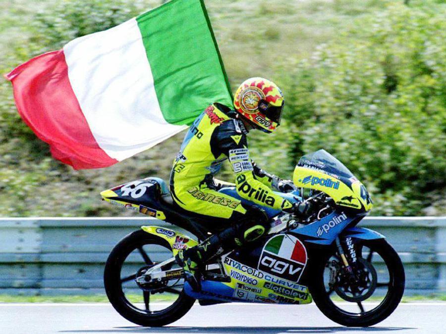 Valentino Rossi festeggia la sua vittoria nella categoria 125 cc sventolando la bandiera italiana al termine della gara a Brno, in una immagine del 18 agosto 1996. (Ansa/Igor Zehl)