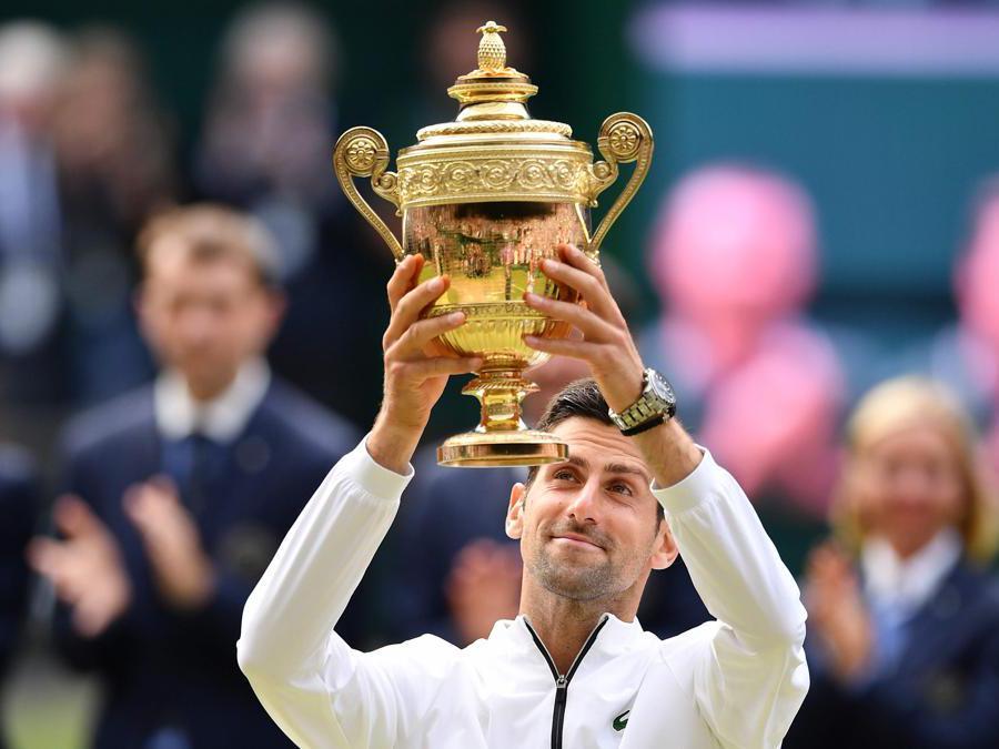Il serbo Novak Djokovic posa con il trofeo mentre celebra la vittoria della finale contro lo svizzero Roger Federer. (Photo by Daniel LEAL-OLIVAS / AFP)