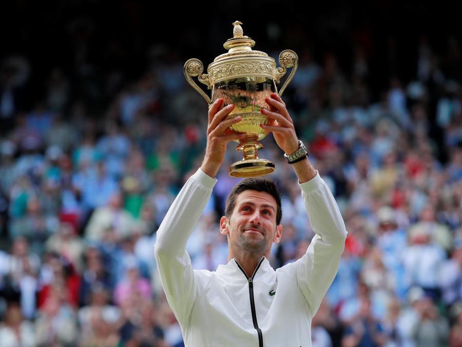 Il serbo Novak Djokovic posa con il trofeo mentre celebra la vittoria della finale contro lo svizzero Roger Federer. REUTERS/Andrew Couldridge