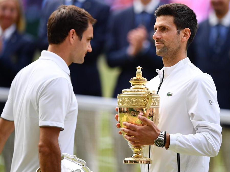Novak Djokovic (destra)  con il trofeo in mano e Roger Federer (sinistra). (Photo by Daniel LEAL-OLIVAS / AFP)