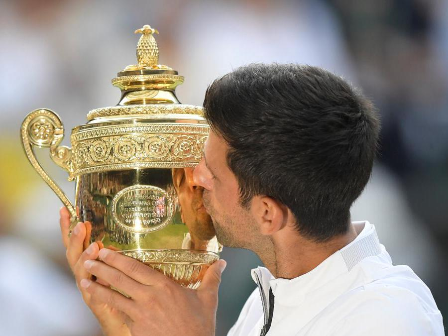 Novak Djokovic bacia il trofeo vinto.  REUTERS/Toby Melville