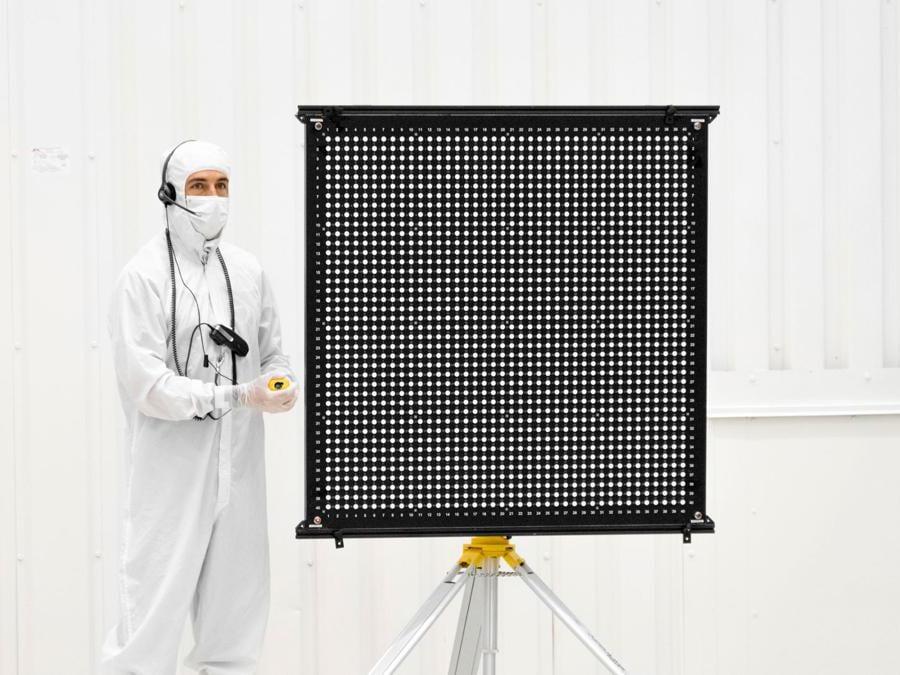 L'ingegnere Chris Chatellier è in piedi accanto a una tavola bersaglio con 1.600 punti. Il tabellone è stato uno dei tanti utilizzati il 23 luglio 2019, nell'High Bay 1 della Facility di assemblaggio di veicoli spaziali presso il Jet Propulsion Laboratory della NASA a Pasadena, in California, per calibrare le telecamere rivolte in avanti sul rover Mars 2020. (Credit: NASA/JPL-Caltech)
