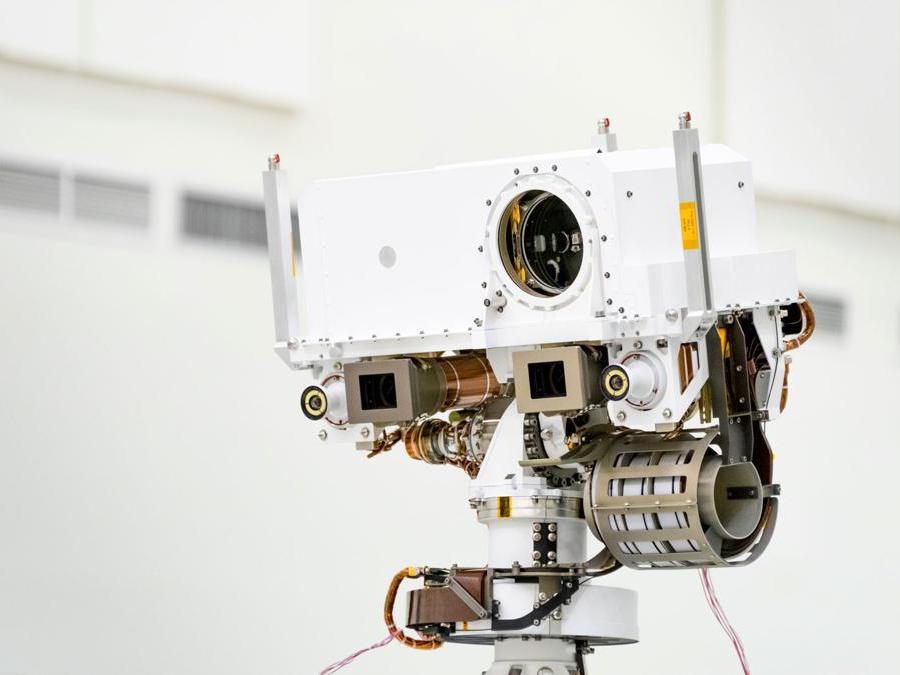 Questa immagine, scattata nell'High Bay 1 della Facility Assembly Assembly presso il Jet Propulsion Laboratory di Pasadena, in California, il 23 luglio 2019, mostra un primo piano della testa dell'albero di telerilevamento di Marte 2020. La testa dell'albero contiene lo strumento SuperCam (la sua lente è nella grande apertura circolare). Nelle caselle grigie sotto la testa dell'albero si trovano i due imager Mastcam-Z. Ai lati esterni di questi imager si trovano le due telecamere di navigazione del rover. (Credit: NASA/JPL-Caltech)